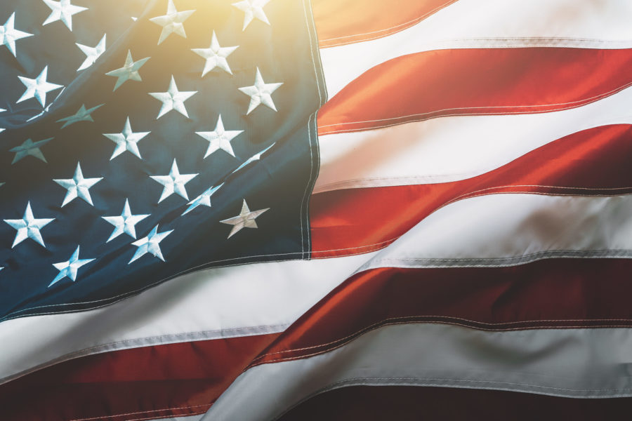 USA flag background. Waving American flag in sunlight flare, close up, vintage toned